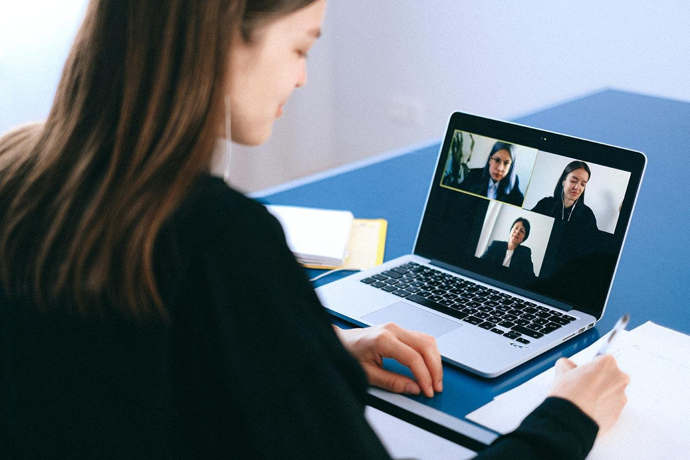 woman works on laptop for meeting over Zoom call