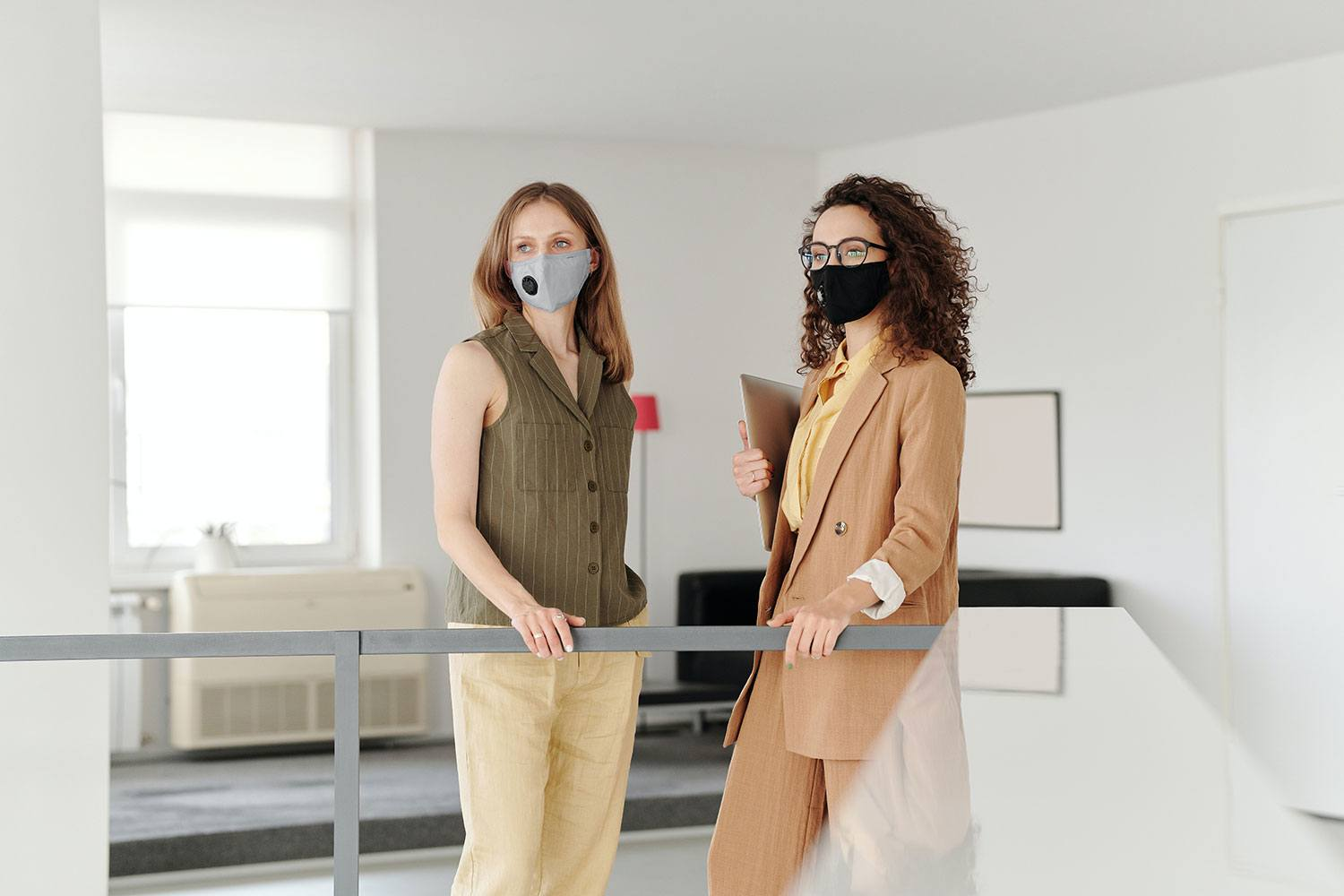 two female co-workers in office with Covid masks on